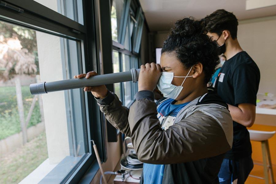 Ethan teste la lunette astronomique qu'il vient d'assembler pour étudier le mouvement de Jupiter et de ses satellites. ©Laurence Geai