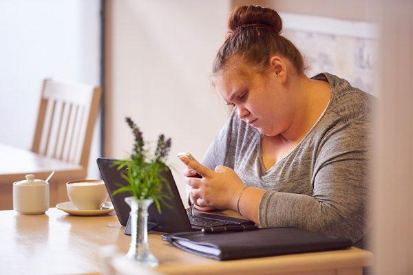 Une jeune fille obèse consulte son smartphone.