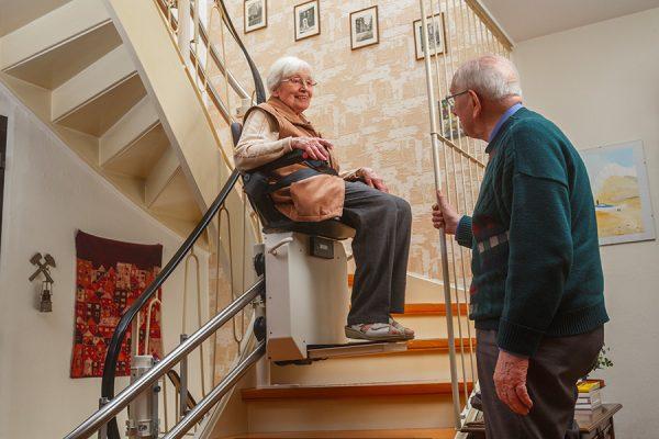 Assise sur un monte-escalier, une vieille dame s'entretient avec un homme de son âge.